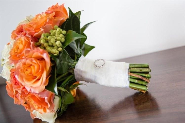 Букет украшенный белой атласной лентой и брошью